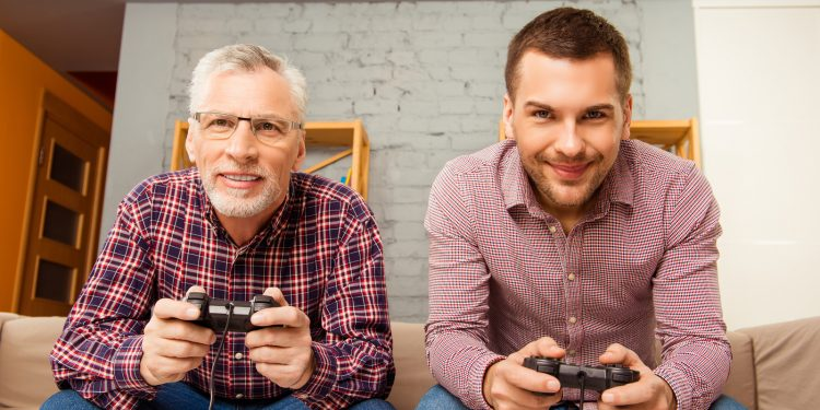 Happy Man And His Father Playing Video Games While Sitting On So