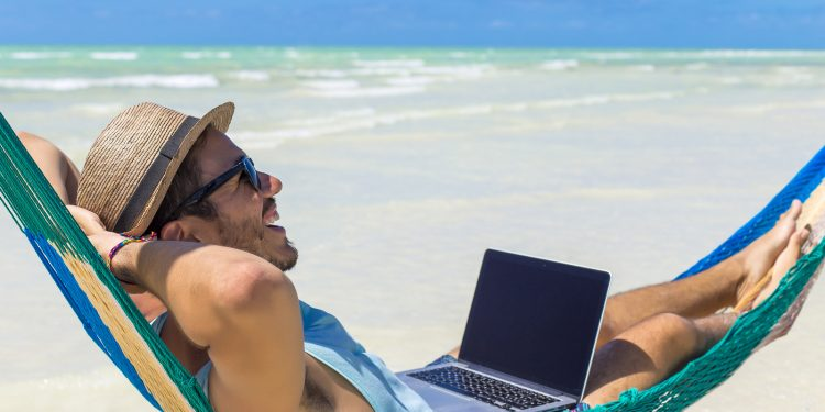Man working with a laptop, on a hammock in the beach. Concept of