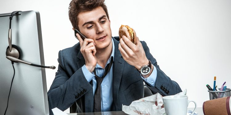 Slacker Man Talking On The Phone While Eating At Work / Modern O